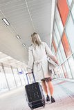 Full length rear view of young businesswoman with luggage walking in railroad station Royalty Free Stock Images