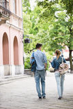 Full length rear view of young college friends talking while walking in campus royalty free stock photos