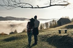 Reached the peak. Full length rear view of young couple embracing while enjoying the perfect view of mountain range Stock Photography