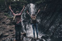 Finally here!. Full length rear view of young couple raising hands while standing near the waterfall Royalty Free Stock Image