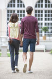 Full-length rear view of young couple walking against building Stock Image