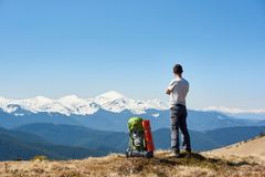 Male hiker with backpack in the mountains. Full length rearview shot of a man resting on top of the mountain after hiking enjoying stunning view of snowy Stock Photos
