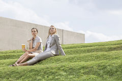 Full length of relaxed businesswomen in formals sitting on grass steps against sky Stock Photos