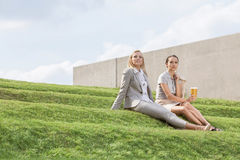 Full length of relaxed businesswomen in formals sitting on grass steps against sky Royalty Free Stock Photography