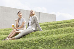 Full length of relaxed businesswomen sitting on grass steps against sky Royalty Free Stock Photography