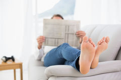 Full length of a relaxed man reading newspaper on sofa Stock Images