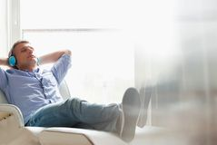 Full-length of relaxed Middle-aged man listening to music at home royalty free stock images