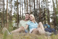Full length of romantic young hiking couple relaxing in forest Stock Photography