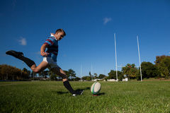 Full length of rugby player kicking ball for goal. Against clear blue sky Royalty Free Stock Photo