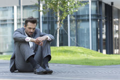 Full length of sad businessman sitting on path outside office Stock Photography