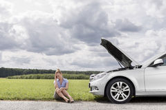 Full length of sad businesswoman sitting by broken down car at countryside Royalty Free Stock Images