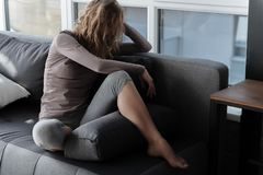 Sorrowful girl situating on couch. Full length sad female sitting on cozy sofa in living room Stock Photos