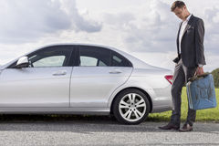 Full length of sad young businessman carrying gas can by broken down car at countryside Stock Photos