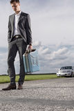 Full length of sad young businessman carrying petrol can with broken car in background at countryside Royalty Free Stock Images