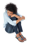 Full length of a sad young woman. Sitting over white background stock image