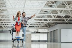 Positive couple entertaining in airport royalty free stock photography