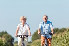 Senior couple looking forward with confidence while riding bicyc Stock Photos