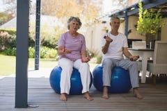 Full length of senior couple exercising at porch Stock Photo