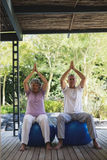 Full length of senior couple meditating sitting together at porch Stock Photos