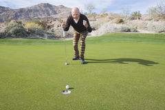 Full length of senior male golfer celebrating a putt at golf course royalty free stock photo