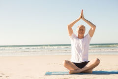 Full length of senior man with eyes closed meditating at beach Stock Photos