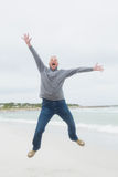 Full length of a senior man jumping at beach Stock Photo