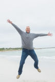 Full length of a senior man jumping at beach Stock Photography