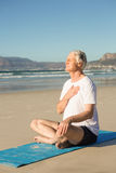 Full length of senior man meditating at beach Stock Images