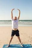 Full length of senior man practicing yoga at beach. On sunny day Stock Photo