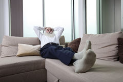 Full length of senior man reclining on sofa with hands behind head at home Stock Images