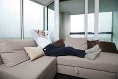 Full length of senior man relaxing on sofa with hands behind head at home Stock Photos