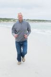 Full length of a senior man running at beach Stock Image