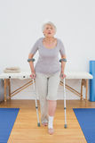 Full length of a senior woman with crutches in hospital gym Royalty Free Stock Photos