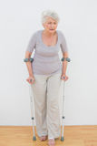Full length of a senior woman with crutches Royalty Free Stock Photos
