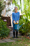 Full length of senior woman standing with watering can on walkway Royalty Free Stock Image