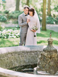 The full-length sensitive portrait of the groom hugging the bride back behind the fountain. Stock Images