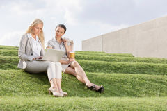 Full length of serious businesswomen looking at laptop while sitting on grass steps against sky Stock Image