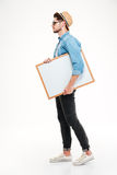Full length of serious man walking and holding blank whiteboard Royalty Free Stock Images