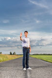 Full length of serious young man holding up hand to stop at country road Royalty Free Stock Photography