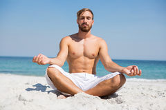 Full length of shirtless man meditating at beach stock photography