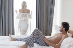 Full length of shirtless young man looking at woman standing by hotel window Stock Photos