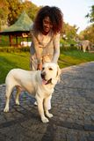 Full-length shot of pretty healthy young lady walking in the morning in park with dog Royalty Free Stock Photo