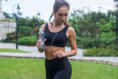 Full length shot of beautiful fitness female model in black sportswear standing on grass in city park and listening to royalty free stock photo