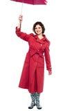 Full length shot of a beautiful lady raising umbrella Royalty Free Stock Images