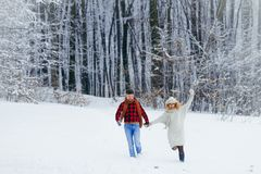 Full-length shot of the cheerfully running couple along the forest covered with snow during the snowfall. Christmas time. Winter holidays Royalty Free Stock Photo