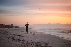 Fit male runner running on the beach. Full length shot of fit male runner running on the beach in morning. Fitness man jogging on the sea shore Stock Image