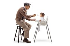 Grandfather feeding a baby with a spoon royalty free stock photo