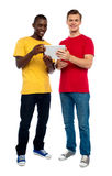 Full length shot of guys operating portable device. Against white background Stock Photos