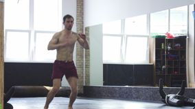 Full length shot of a ripped mma fighter practicing hich kicks at the gym stock footage