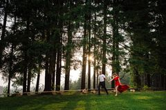 Full-length shot of the happy elegant couple holding hands while running along the green forest during the sunset. Royalty Free Stock Photos